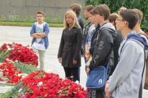 Young Russians place flowers and ponder humanity's unflattering past.