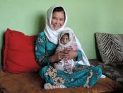 Jamila, age 11, holds a neighbor's newborn. PHOTO: Henrietta Cullinan